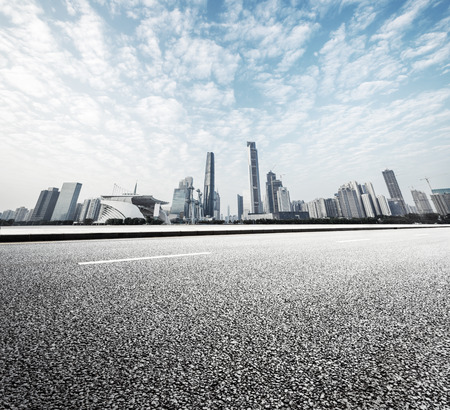city streets: modern road with skyline and cityscape background Stock Photo