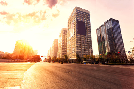 empty street: skyline,urban road and office buildings at sunset Stock Photo
