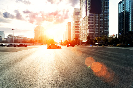 road travel: skyline,urban road and office buildings at sunset Stock Photo