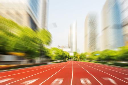 pista de atletismo: línea de carrera a pie en la carretera de la ciudad moderna con el paisaje urbano como fondo, el concepto moderno de la competencia empresarial.