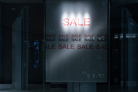 window display: sale poster light up in fashion shop display window