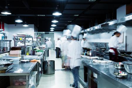 Cocina moderna y cocineros ocupados en el hotel