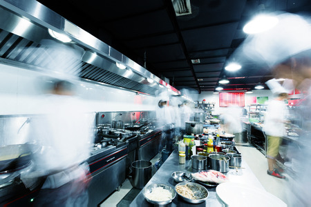chef kitchen: Modern kitchen and busy chefs in hotel Stock Photo