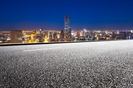 Empty road with modern city skyline