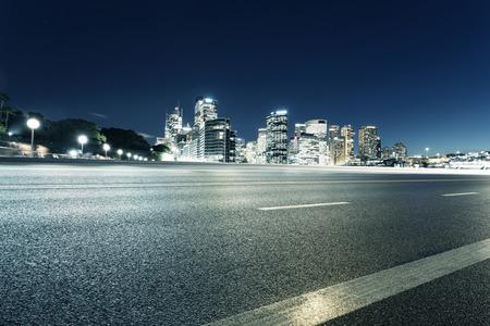 Lege asfaltweg en verlichte moderne stadsbeeld achtergrond in de nacht