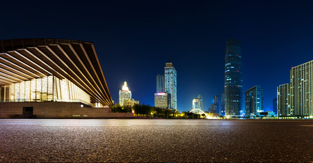 city light: Empty asphalt road and modern skyline at night