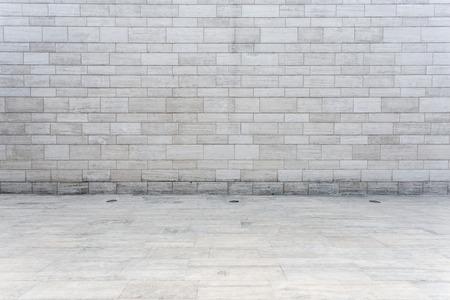 白いレンガの壁と空の砂岩道