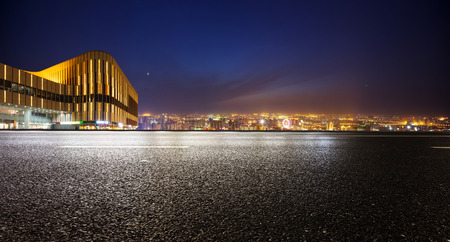 panoramic sky: Empty asphalt road and modern skyline at night