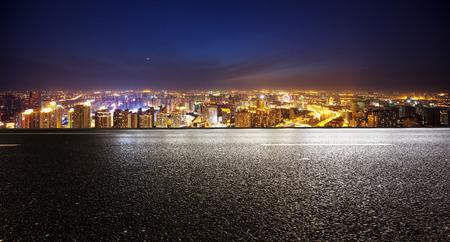 nacht: Leere Asphaltstraße und moderne Skyline bei Nacht