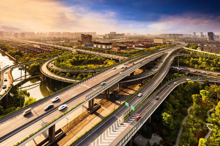 Elevated overpass with skyline of modern city during sunset. Stok Fotoğraf