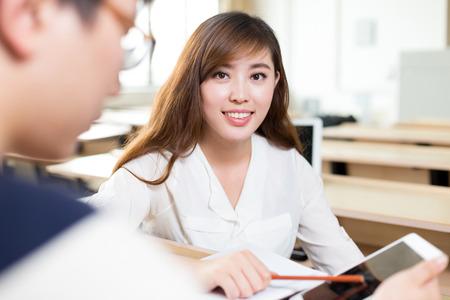 tutor: Dos estudiantes asiáticos discuten contenidos en la tableta Foto de archivo