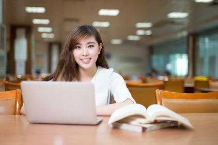 alumno estudiando: Estudiante femenino asi�tico que estudia en biblioteca con el ordenador port�til