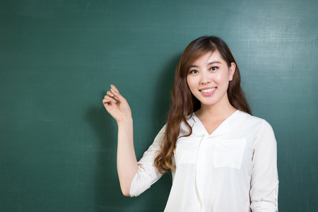 Asian woman standing in front of blackboard with gesture Stock Photo