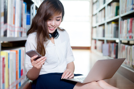 bookshelf digital: Asian female student using laptop and mobile phone in library Stock Photo