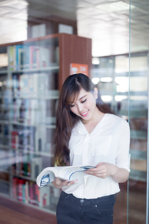 library book: Asian beautiful female student holding book in library