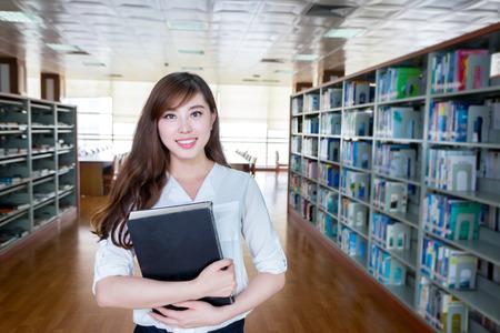 biblioteca: Estudiante femenino asiático que sostiene el libro en la biblioteca Foto de archivo
