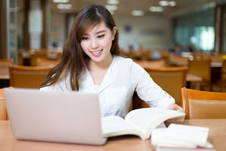 Asian female student studying in library with laptop
