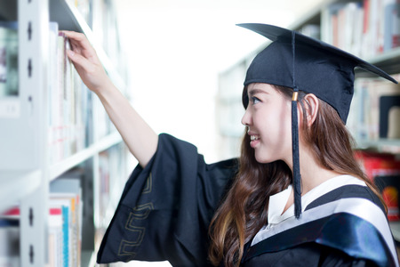 postgraduate: Asian female student looking for book in library Stock Photo