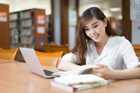 alumno estudiando: Asian female student studying in library with laptop