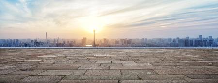 piso piedra: Horizonte y los edificios con plaza de ladrillo vacía panorámica Foto de archivo