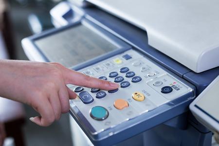 impresora: mano pulse el botón en el panel de la impresora Foto de archivo