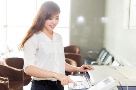 fotocopiadora: hermosa mujer asiática con la impresora en la oficina