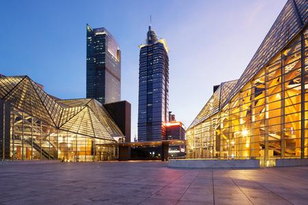 Verlichte modern gebouw exterieur en lege straat Redactioneel