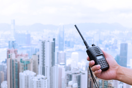 cb: hand holding walky talky with cityscape as background