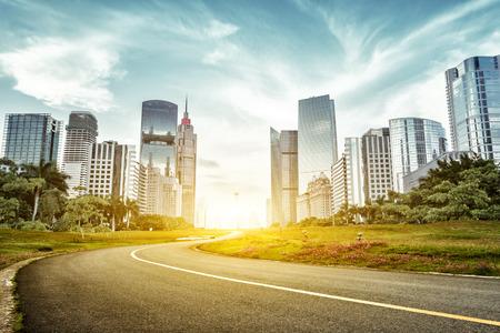 lege asfalt weg met bomen opzij en wolkenkrabbers in zonnestraal