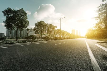 sol radiante: carretera de asfalto vac�a con �rboles bajo el sol Foto de archivo