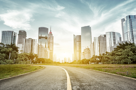 asphalt: empty asphalt road with trees aside and skyscrapers under sunbeam Stock Photo