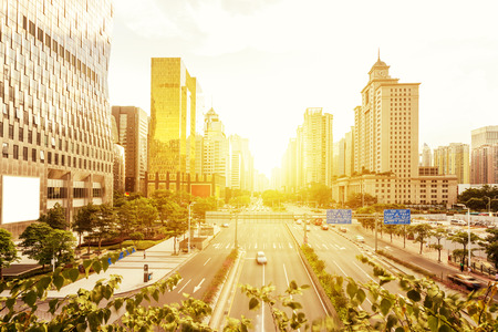 golden light: modern city street and skyscrapers under sunset