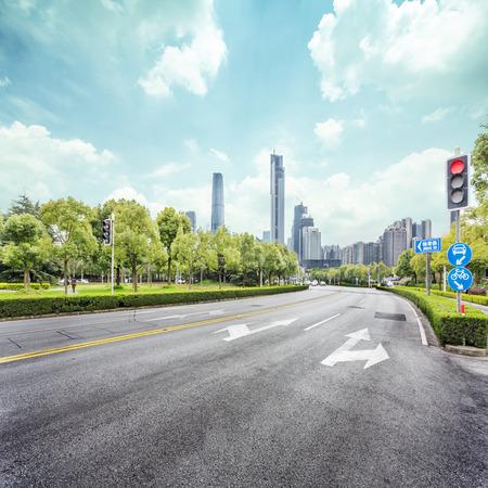 lege straat met bomen opzij en wolkenkrabbers als achtergrond