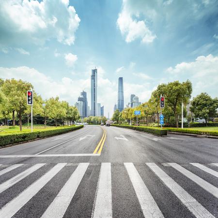 cebra: carretera vacía, con el paso de cebra y los rascacielos en la ciudad moderna
