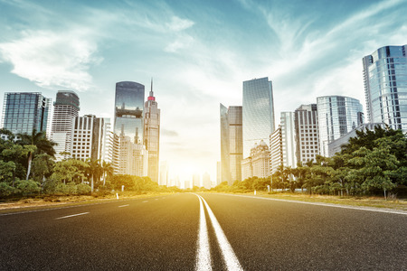empty asphalt road with trees aside and skyscrapers under sunbeam 写真素材