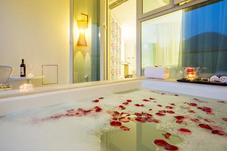 bath room: rose floating on water in bathtub of modern bathroom with window