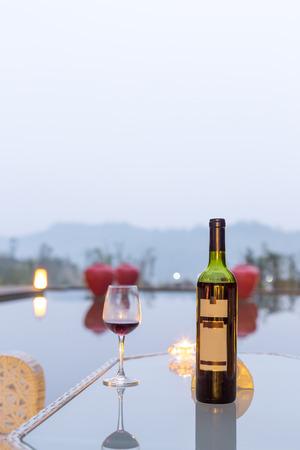 vidrio: vino tinto y la taza en la mesa cerca de la charca en el cielo sombr�o