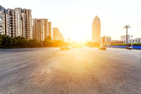 buildings city: sun skyline and traffic on urban road through city buildings Stock Photo