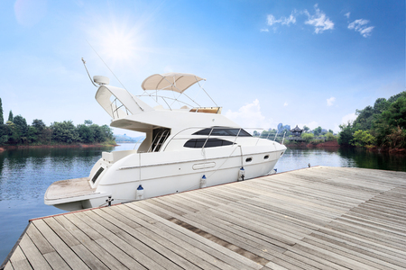 wooden dock: white yacht along wooden dock in sunny sky Stock Photo