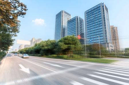 urban road: sun skyline and traffic on urban road through city buildings Stock Photo