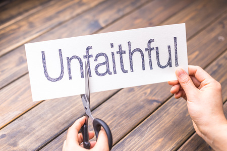 unfaithful: woman cuts white paper with word unfaithful on table Stock Photo
