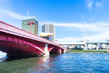 bridge over water: red bridge over water to modern buildings with blue skyline in tokyo