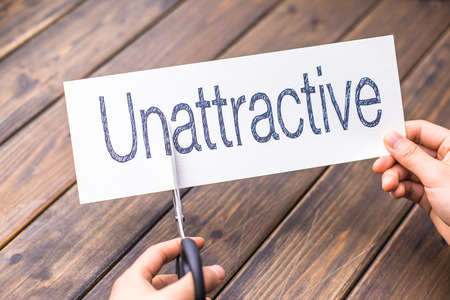 unattractive: woman cuts white paper with word unattractive on table