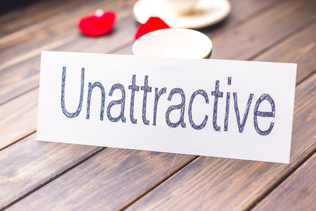 unattractive: white paper with word unattractive against elegant coffee cup in cafe