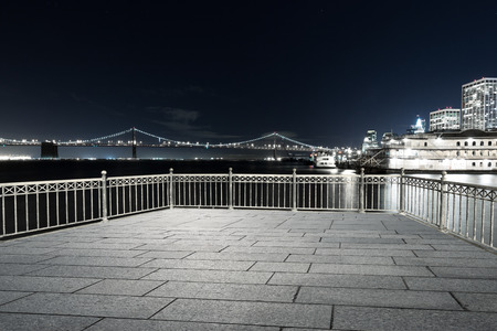 bridge over water: night scene of suspension bridge over water and modern buildings in san francisco on view from empty floor