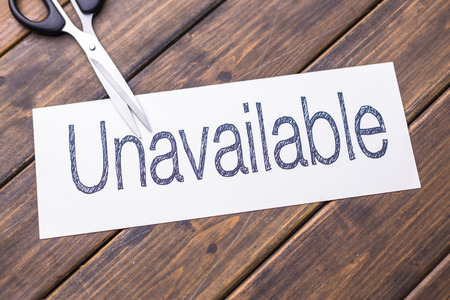 unavailable: white paper with word unavailable and scissors on table