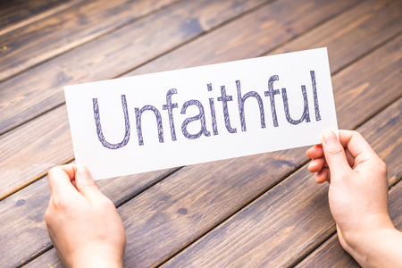 unfaithful: hands hold white paper with word unfaithful Stock Photo