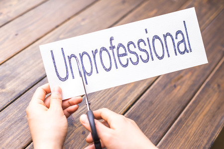 unprofessional: woman holds paper with word unprofessional in office
