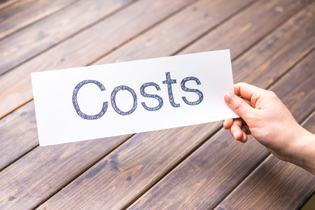 price cutting: hand hold white paper with word cost