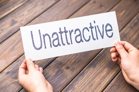 unattractive: hands hold white paper with word unattractive